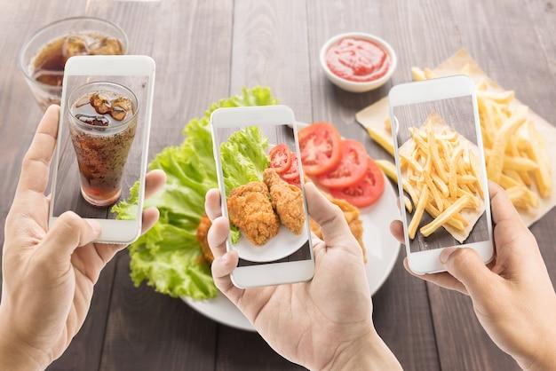 Freunde, die mit smartphones fotos von brathähnchen, pommes und cola machen