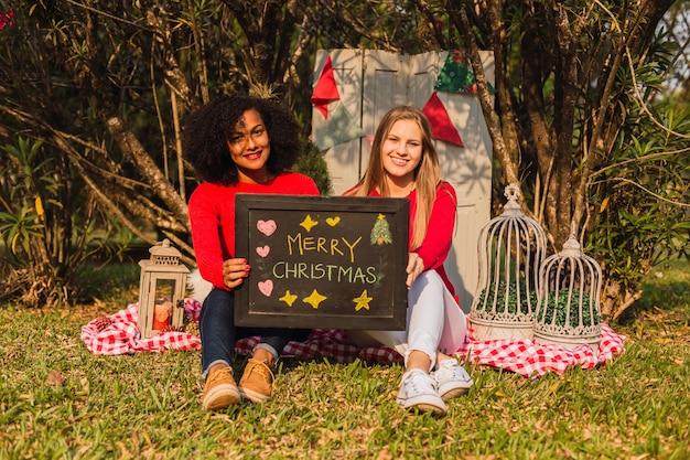 Freunde, die mit weihnachtsbotschaft sitzen