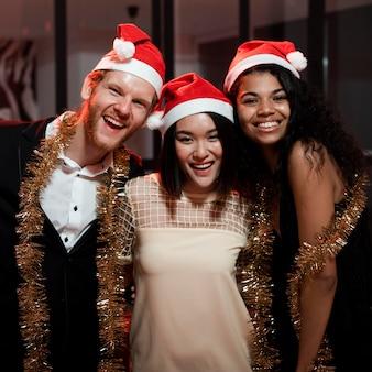 Freunde, die mit weihnachtsmützen feiern