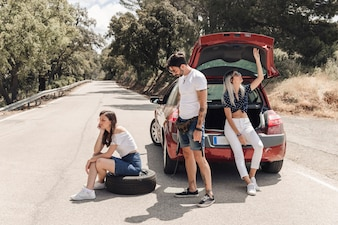 Freunde, die nahe dem Zusammenbruchauto auf Straße sitzen