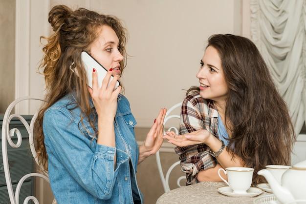 Freunde, die per telefon sprechen, während tee getrunken wird