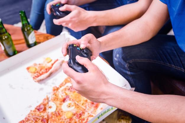 Freunde, die pizza essen und auf der konsole spielen