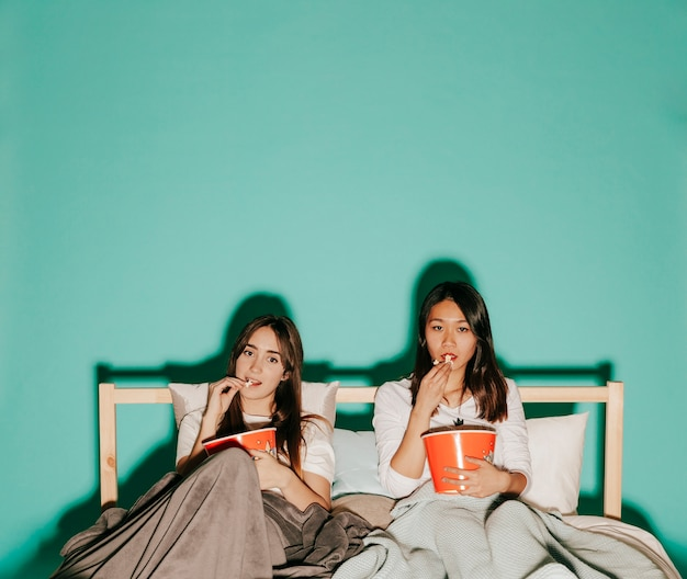 Freunde, die popcorn auf bett essen