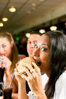 Freunde, die schnellimbiß in einem restaurant essen
