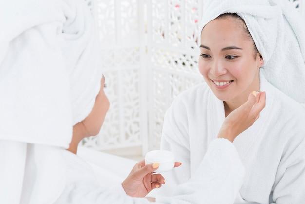 Freunde, die schönheitscreme in einem badekurort verwenden