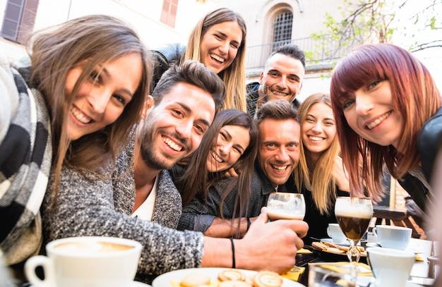 Freunde, die selfie an trinkendem cappuccino des bar-restaurants und am irischen kaffee nehmen