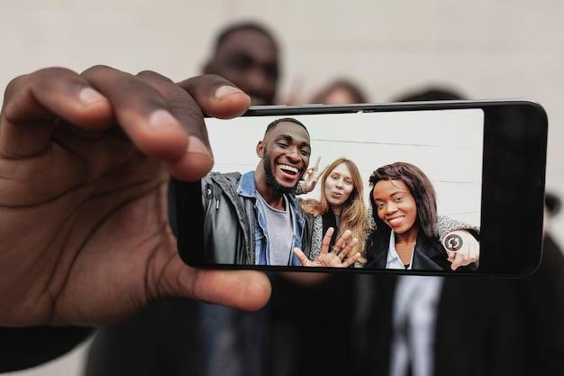 Freunde, die selfie mit smartphone nehmen