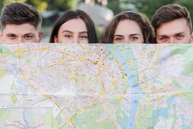Freunde, die sich mit stadtplan verstecken