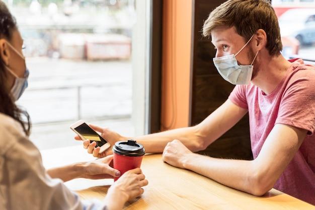 Freunde, die sich unterhalten, während sie medizinische masken in einer kneipe tragen