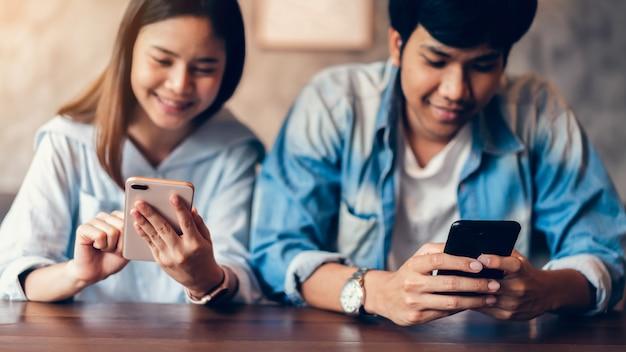 Freunde, die smartphone auf café, während der freizeit verwenden.
