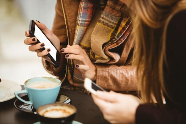 Freunde, die smartphone im café betrachten
