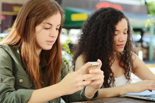 Freunde, die smartphone und laptop verwenden.