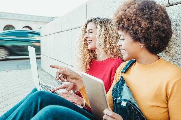 Freunde, die smartphone und technologie in den straßen der stadt einsetzen konzept der telefonie und der kommunikationen bei jungen leuten