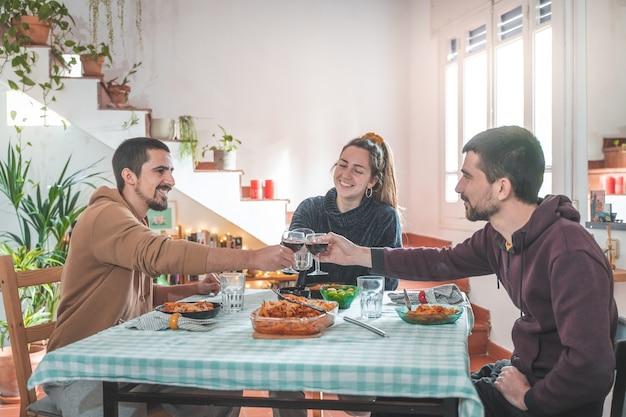 Freunde, die spaß beim abendessen am esstisch zu hause haben fröhliches essen, toasten und genießen