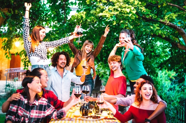 Freunde, die spaß beim toasten von rotwein auf der gartenparty im freien haben