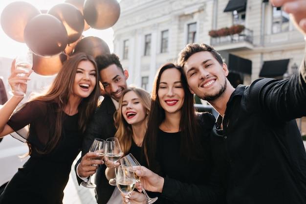 Freunde, die spaß haben und draußen champagner trinken