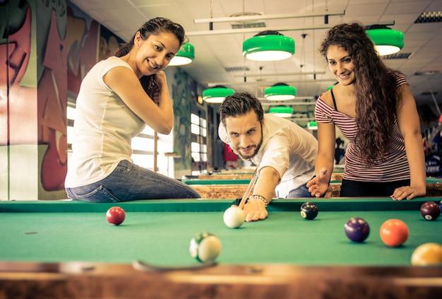 Freunde, die spaß im pool-arcade-raum haben