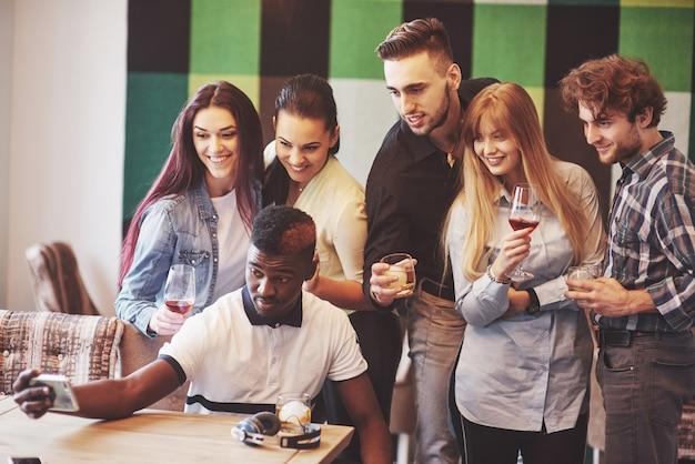 Freunde, die spaß im restaurant haben. drei jungen und drei mädchen machen selfie und lachen. auf vordergrundjunge, der smartphone hält. alle tragen freizeitkleidung
