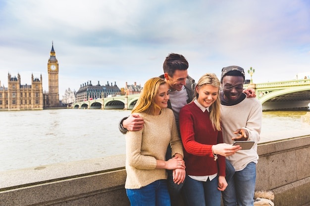 Freunde, die spaß mit smartphone bei big ben in london haben
