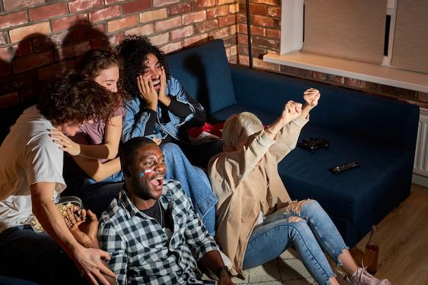 Freunde, die sport gucken und das ziel feiern, während sie den wettbewerb im fernsehen online übersetzen. jubel für lieblingsteam, unterhaltungskonzept