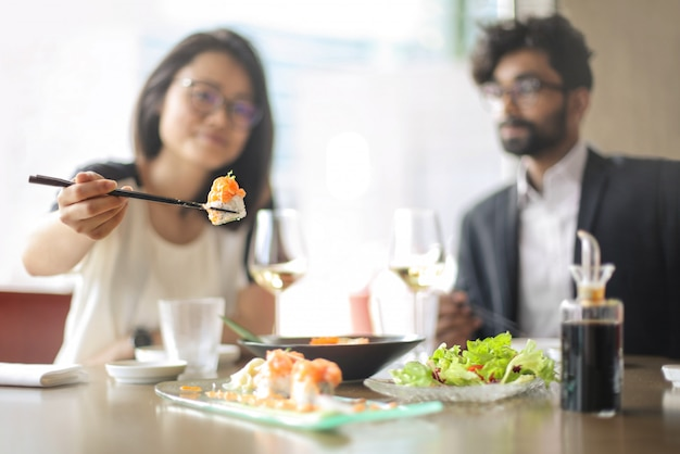 Freunde, die sushi in einem restaurant schmecken