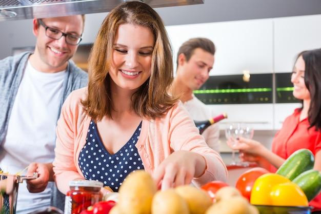 Freunde, die teigwaren und fleisch in der inländischen küche kochen
