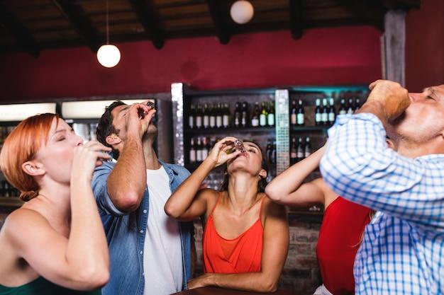 Freunde, die tequila am tisch trinken