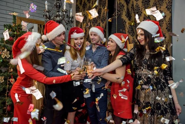 Freunde, die um mitternacht auf der neujahrsparty mit champagner anstoßen
