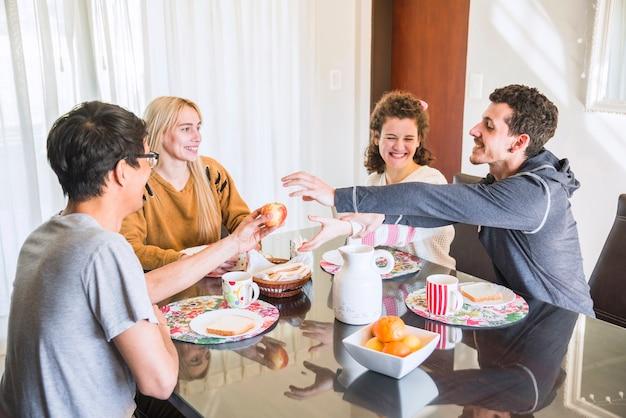 Freunde, die versuchen, apfel von der hand des mannes beim frühstück zu erhalten