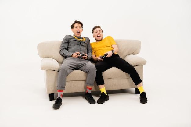 Freunde, die videospiele spielen, während sie zeit zusammen verbringen, sitzen auf dem kleinen sofa und betrachten die front lokal auf weißer wand