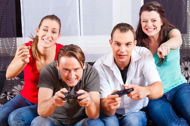 Freunde, die vor spielkonsolenkasten sitzen