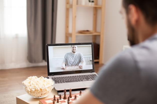 Freunde, die während der quarantäne bei videoanrufen schach sprechen und spielen.