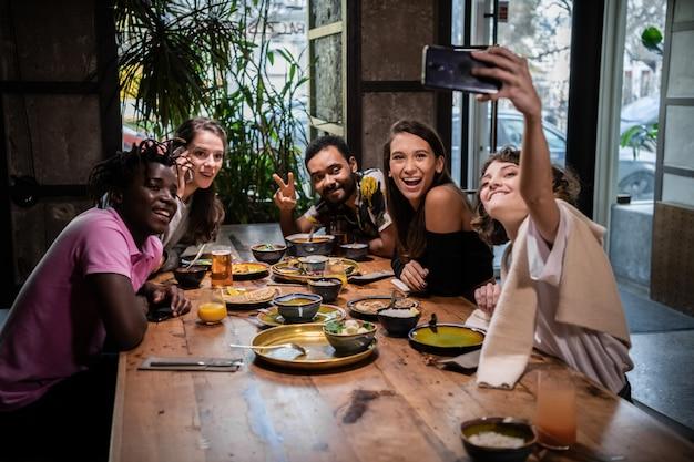Freunde, die während einer dinnerparty selfies in einem café machen