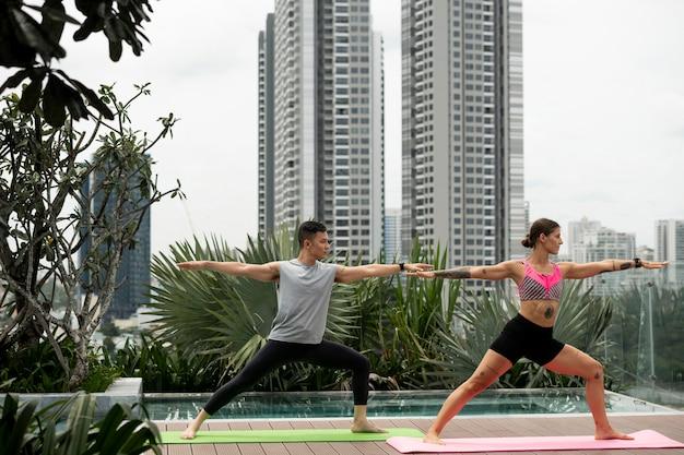 Freunde, die yoga auf der matte im freien neben dem pool praktizieren