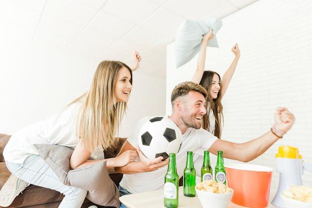 Freunde, die zu hause aufpassenden fußball feiern