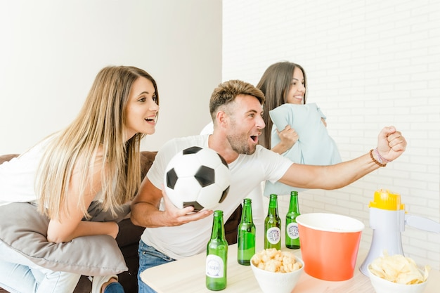 Freunde, die zu hause fußball aufpassen zujubeln