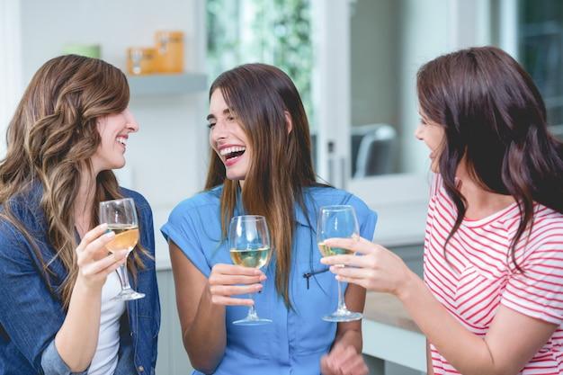 Freunde, die zu hause glas wein halten