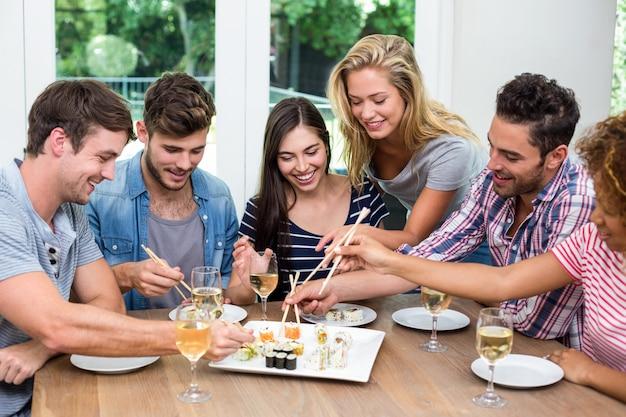 Freunde, die zu hause wein und sushi genießen