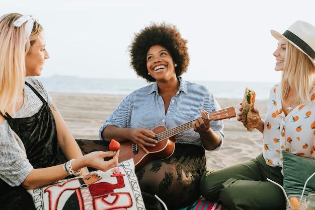 Freunde, die zusammen an einem strandpicknick singen
