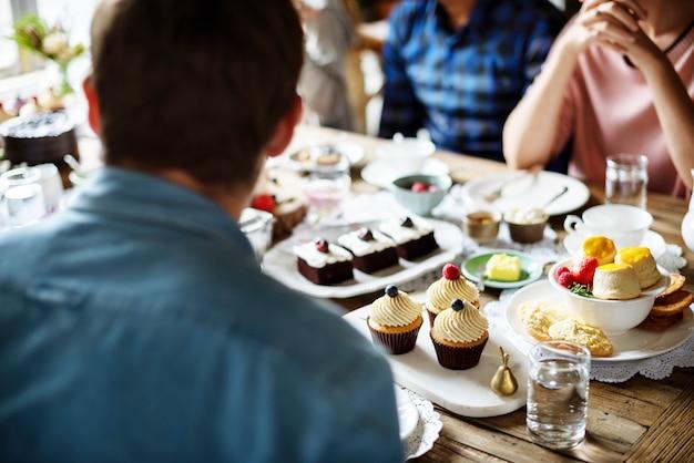 Freunde, die zusammen auf der teeparty essen kuchen essen genussglück