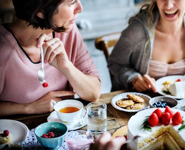 Freunde, die zusammen auf der teeparty essen, kuchen essen genussglück