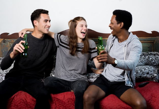 Freunde, die zusammen auf sofa watching sport sitzen