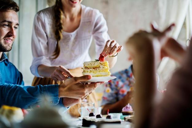 Freunde, die zusammen auf teeparty essen kuchen-genussglück sammeln