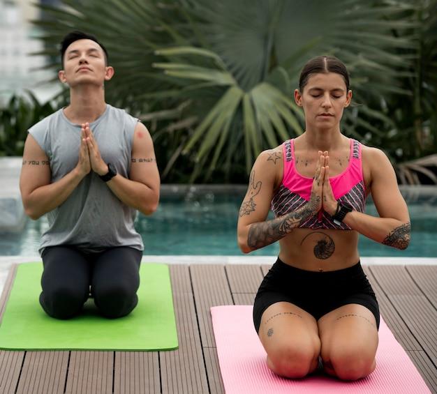 Freunde, die zusammen draußen am pool yoga praktizieren