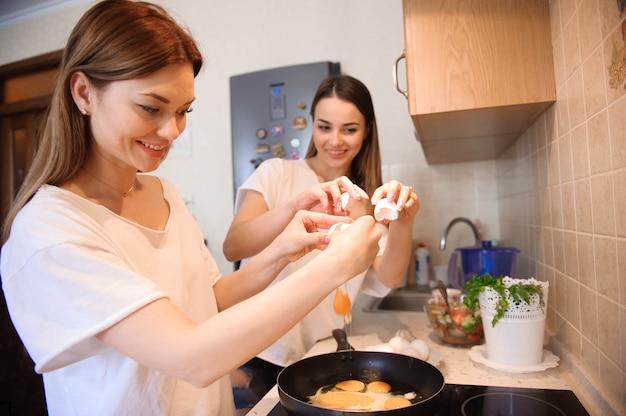 Freunde, die zusammen frühstück zubereiten und in der küche essen.