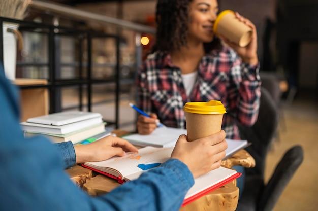 Freunde, die zusammen hausaufgaben machen, während sie kaffee trinken