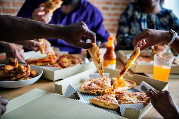 Freunde, die zusammen pizza zu hause essen