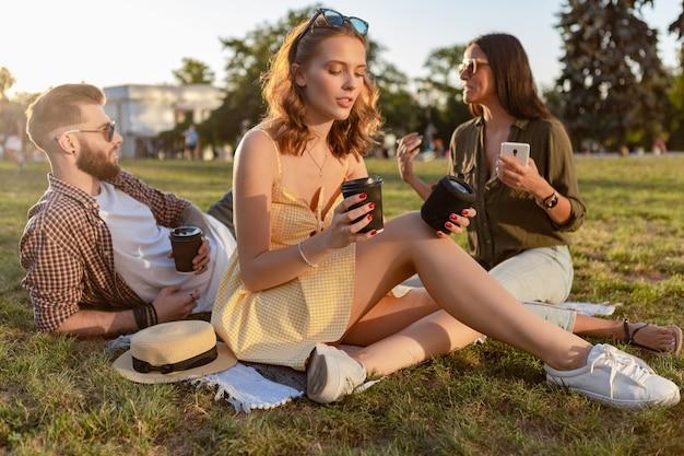 Freunde, die zusammen spaß im park haben, lächeln, musik auf einem kleinen drahtlosen lautsprecher hören, kaffee trinken