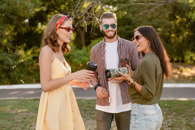 Freunde, die zusammen spaß im park haben und lächeln, musik auf drahtlosen lautsprechern hören?