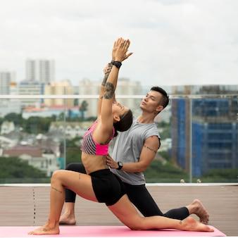 Freunde, die zusammen yoga im freien machen